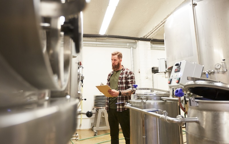 A man dressed in flannel inspects brewing equipment at small brewery